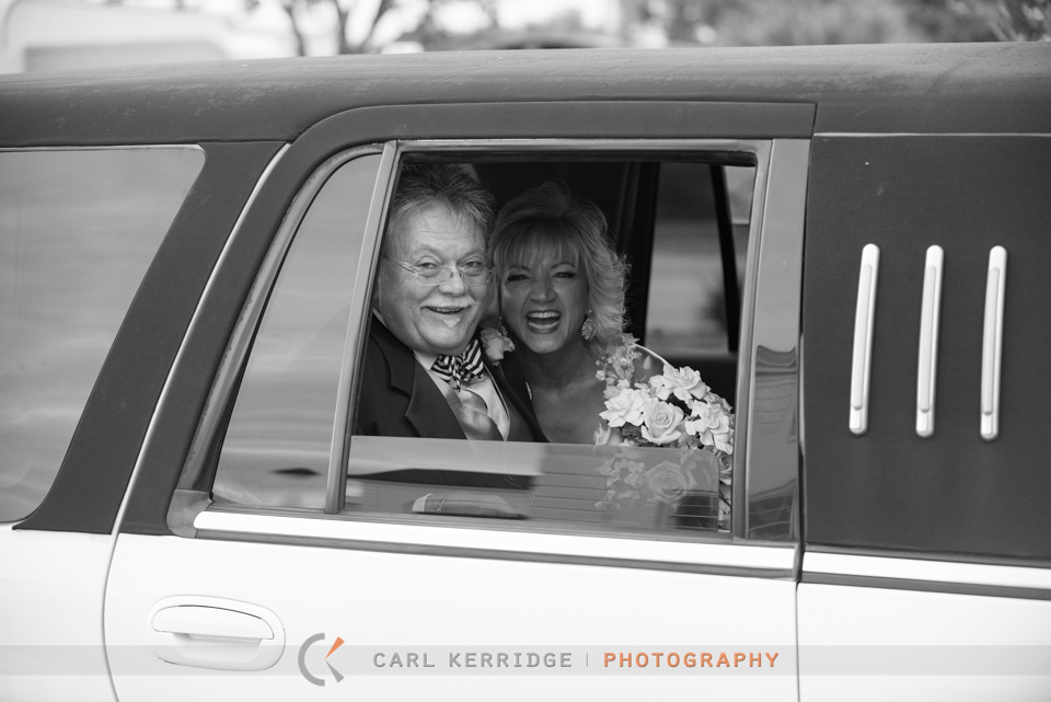 Happy couple in the limousine looking out the window