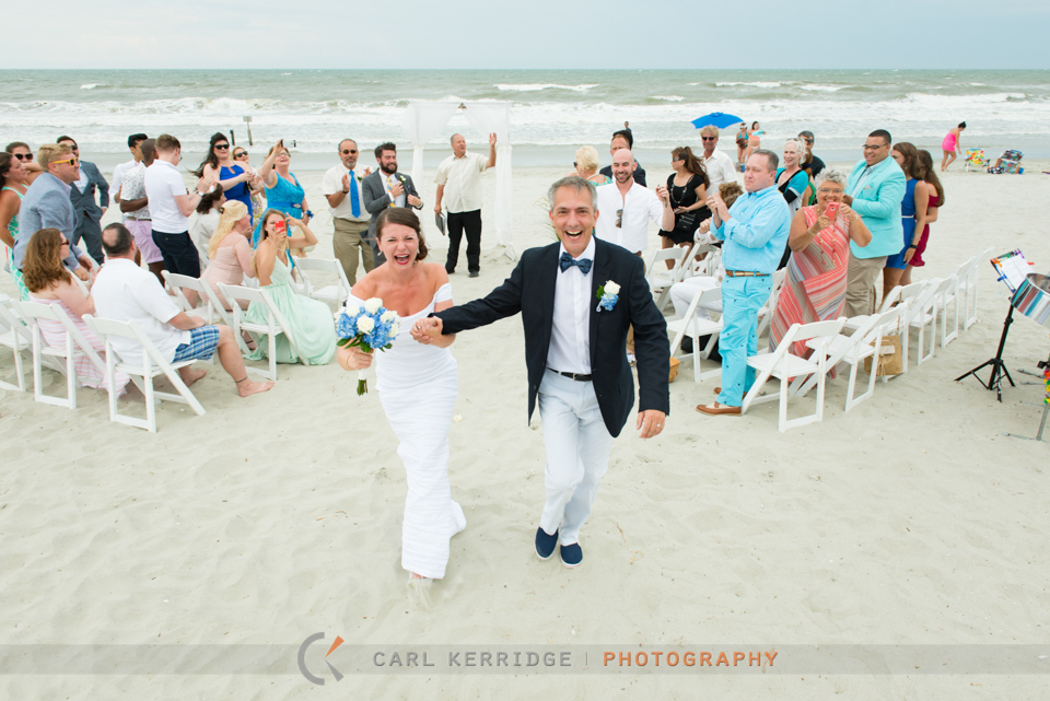 Happy couple walking away from their beach ceremony in North Myrtle Beach