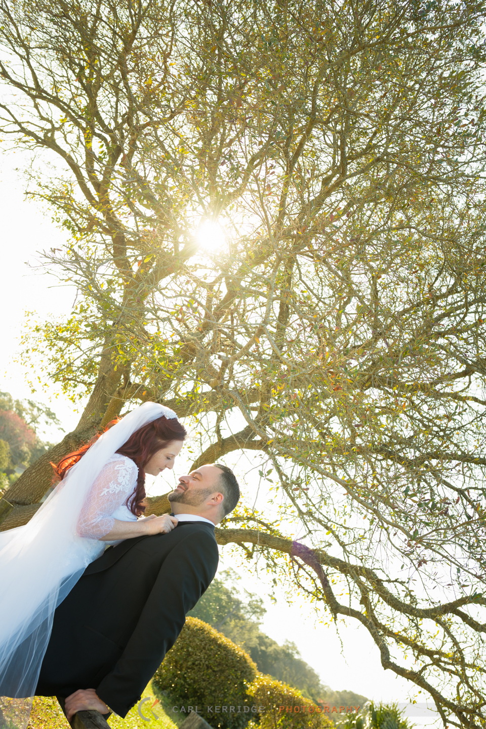 Myrtle Beach wedding, portraits, bride and groom fine art photography, bride looking lovingly at her groom under a blossoming tree's branches, sun shining through branches, groom leaning against fence at Hilton Myrtle Beach