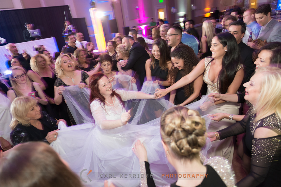 Myrtle Beach wedding, reception at Hilton Myrtle Beach, female guest dance around the bride, picking up corners of her dress and laughing with her. Bride is dancing and smiling, groom hugs his mother in the background