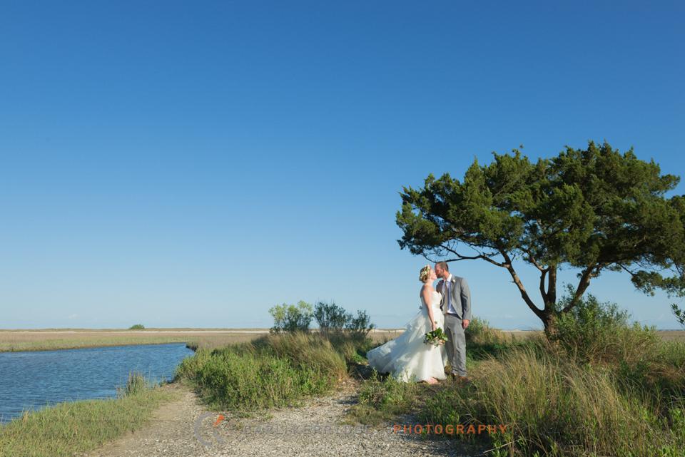 southern wedding, south carolina, wedding, couple, wedding photography, couple kissing, under a tree, blue skies, marsh, beautiful landscape, flower crown