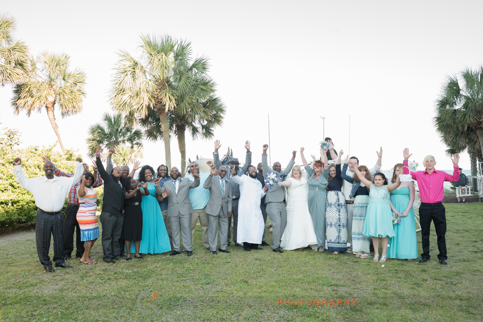 the bride, groom, and their familes pose with the horse and carriage after the couple's Wedding Carriage Ride