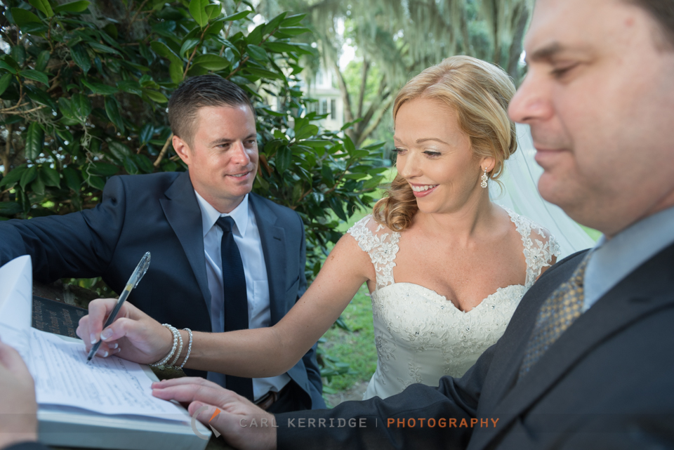 Bride signing her marriage license under the live oaks at Wachesaw Plantation