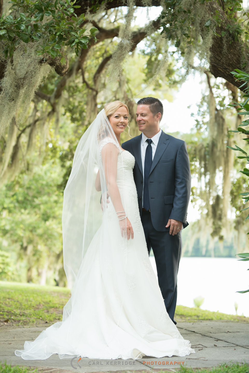 Bride and groom pose beneath the live oaks at Wachesaw Plantation