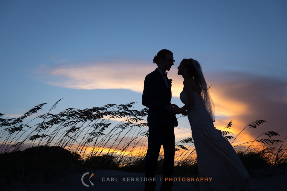 the wedding couple are silhouetted against a gorgeous sky at the dunes club in myrtle beach