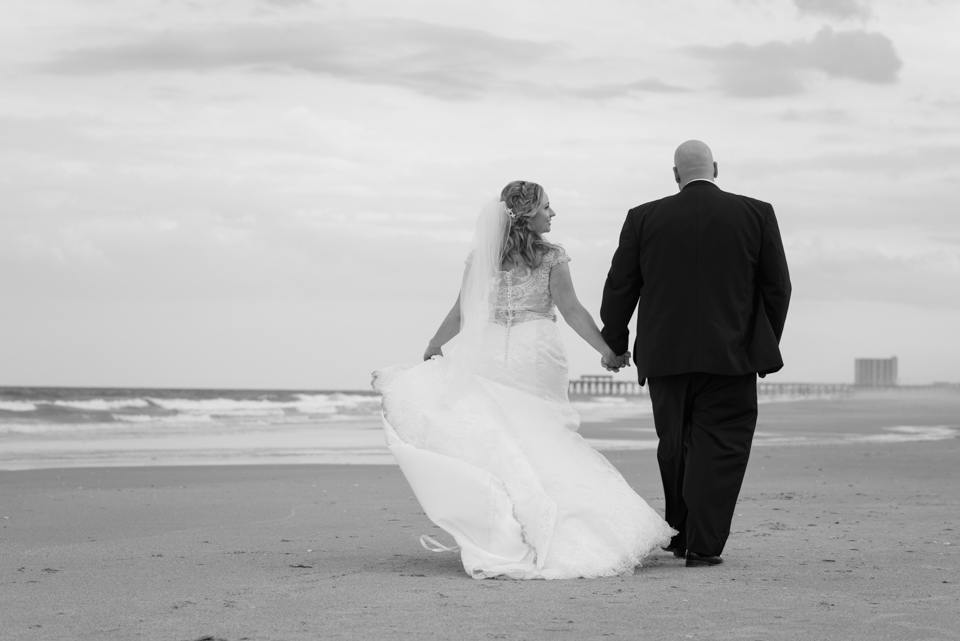bride and groom walk down the beach with overcast skies