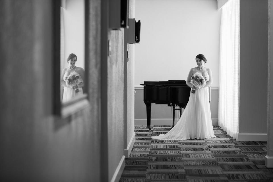bride poses in hallway with her reflection in picture frame before her wedding ceremony