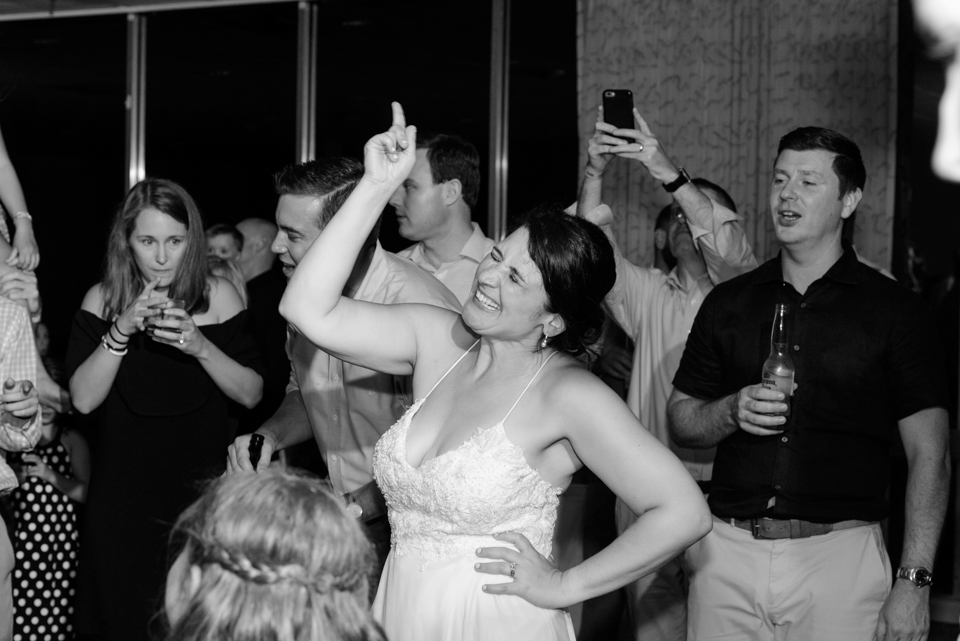 bride points up to the sky during the wedding reception