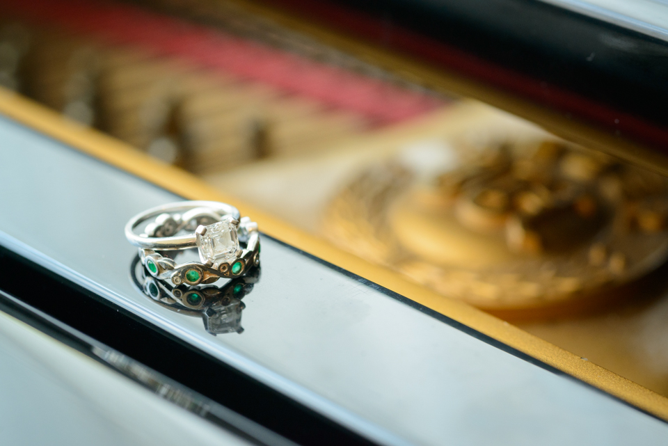 engagement ring and wedding band rest onto of a piano for a macro shot